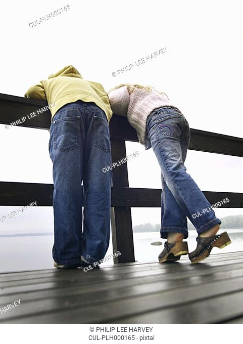 Young boy and young girl leaning over a railing by a lake