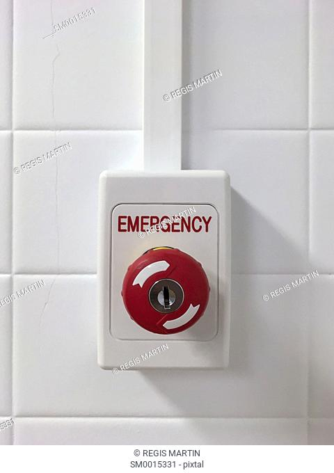 A red Emergency push button on a white wall