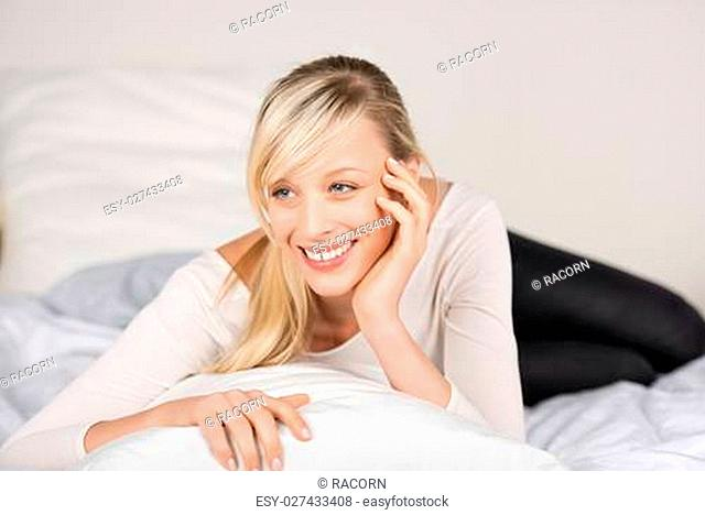Happy fresh female looking at something while lying on her bed