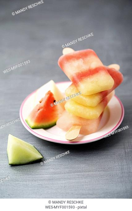 Plate with stack of different homemade melon ice lollies