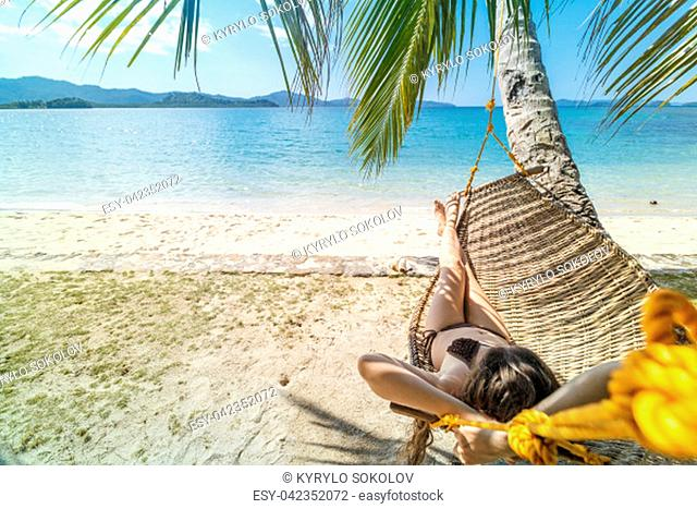 Summer vacations concept, Woman in swimsuit is relaxing in a hammock on a tropical beach El Nido on the Palawan island, Philippine