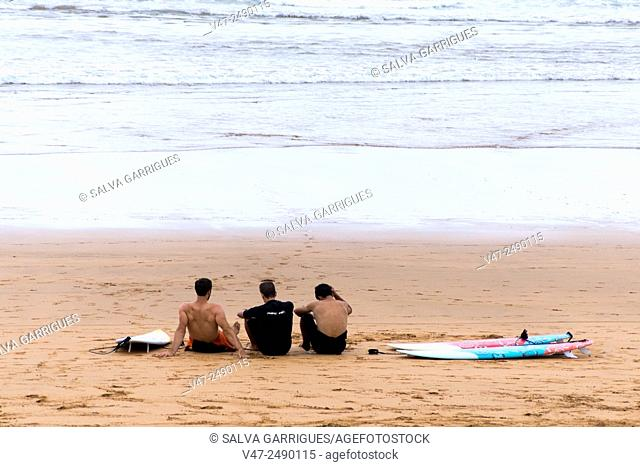 Three surfers relaxing on the sandy beach of Zarautz, Guipúzcoa, Basque Country, Spain, Europe
