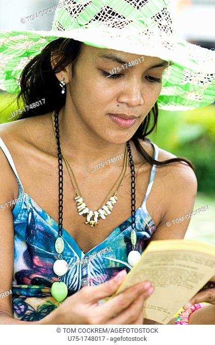 Young woman reading book in Fort San Pedro, Cebu City, Philippines