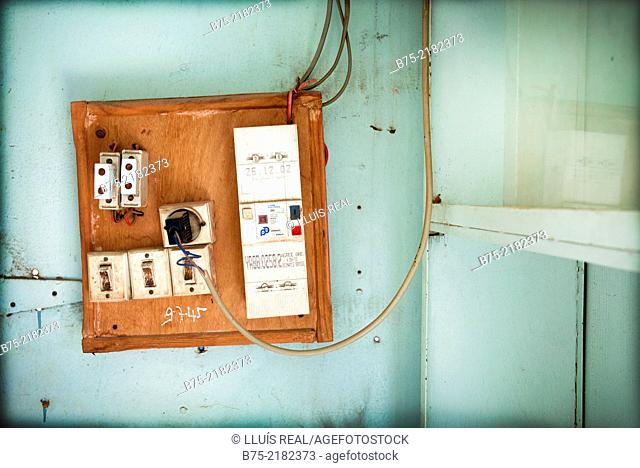 Closeup of a wooden panel with electrical outlets and several switches hanging on a blue wall Morocco, Africa