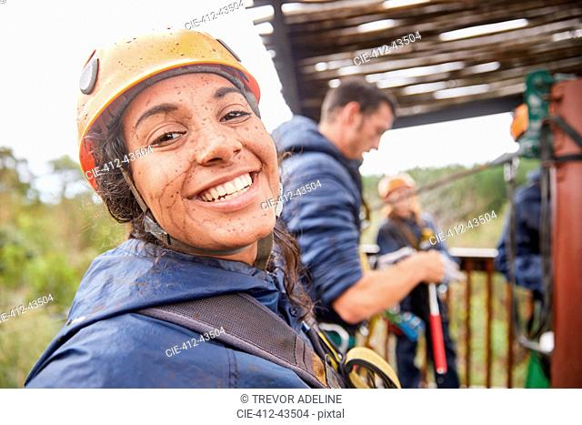 Portrait enthusiastic, muddy young woman enjoying zip lining