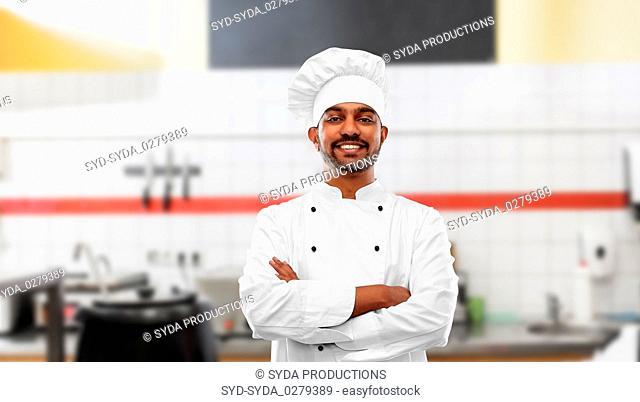 happy indian chef in toque at restaurant kitchen