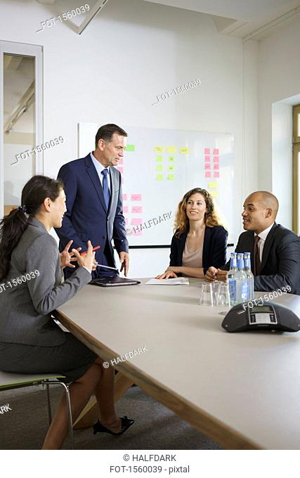 Happy business people discussing in meeting at conference table