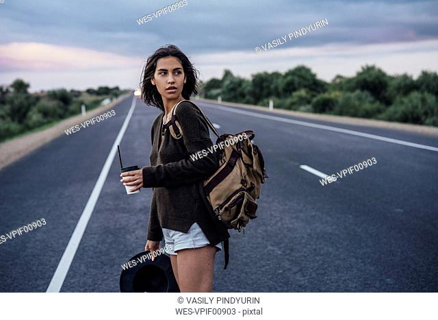 Portrait of young hitchhiking woman with backpack and beverage standing on lane
