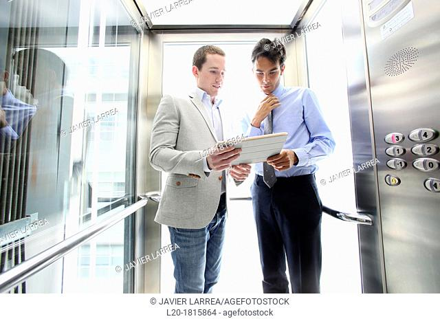 Two executives in elevator, using a digital tablet