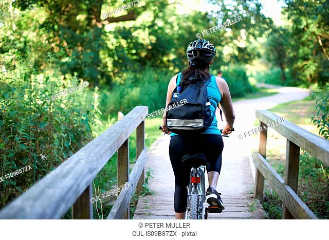 Cyclist riding across bridge