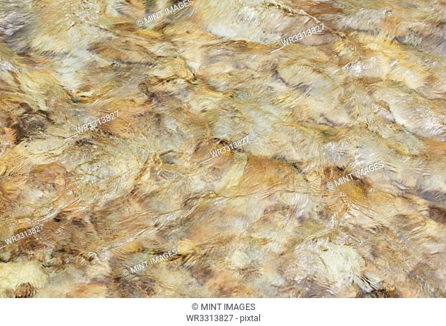 Clear river water flowing over boulders, natural pattern
