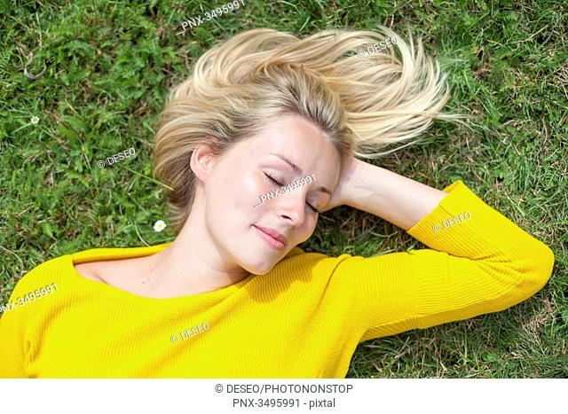 Portrait of a pretty blond woman lying down in the park with closed eyes