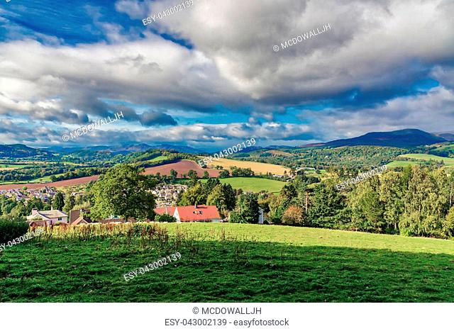 The Scottish hillside looking over some residential housing onto the fields hillside and distant mountains that watch over the highland village of Crieff in...