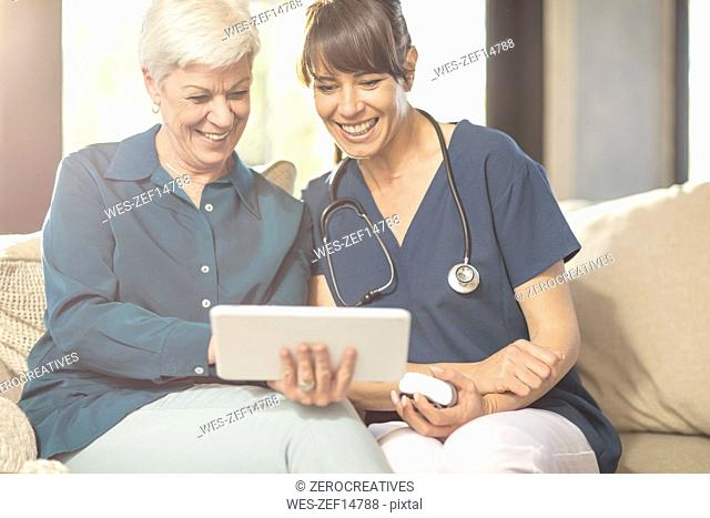 Senior woman sharing tablet with nurse at home