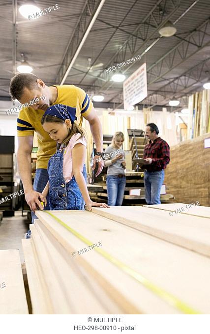 Father and daughter measuring wood planks in home improvement store