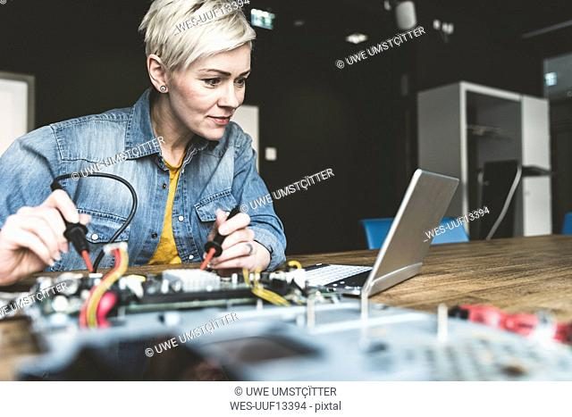 Woman working on computer equipment looking at laptop