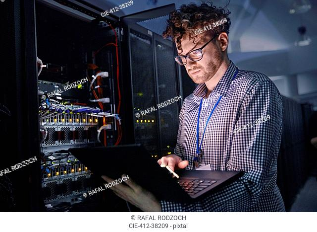 Focused male IT technician working at laptop in dark server room