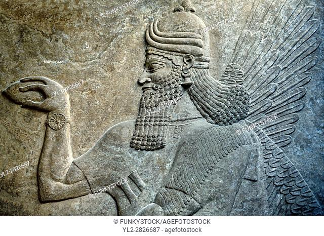 Assyrian relief sculpture panel of a protective spirits, from Nimrud, Iraq. The spirit is holding a symbolic fir cone and is sprinkling holy water