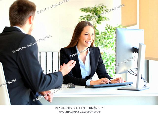 Agent attending to a client introducing data in a desktop computer at office