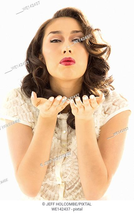 Beautiful young woman in white blouse, gently blowing a kiss off palms of hands directly forward