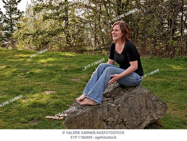 This image is a young Caucasian woman wearing blue jeans and a black shirt, laughing while sitting barefoot on a large rock Very natural looking