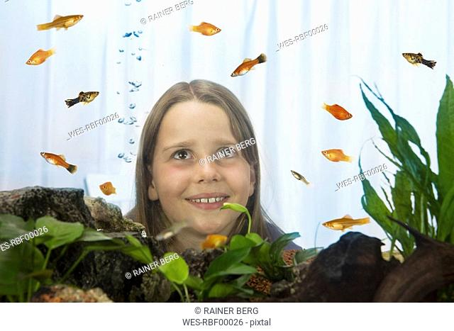Girl 8-9 watching fish, view through fish tank