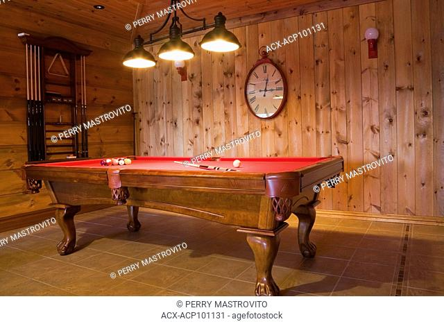 Wooden claw foot with red felt billiard table in playroom adjacent to the family room on ground floor inside a cottage style flat log profile and timber home