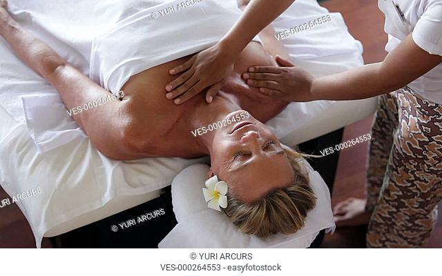 Topview of a mature woman receiving a relaxing chest and shoulder massage