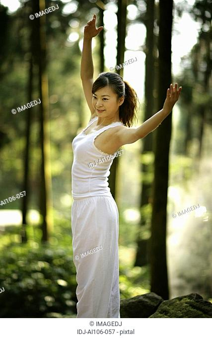 View of a young woman exercising in a forest
