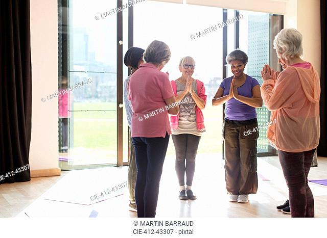 Smiling senior women exercising, practicing yoga in sunny studio