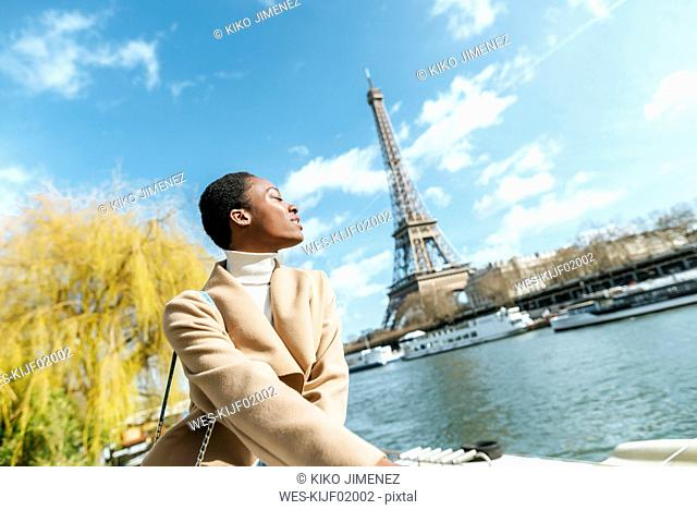 France, Paris, Woman with closed eyes at river Seine with the Eiffel Tower in the background