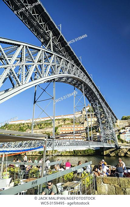 outdoor terrace bar cafe and landmark bridge in ribeira riverside area of porto portugal