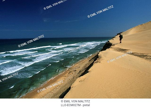 Long Shot of a Hiker Walking Along a Sand Dune Next to the Ocean  Woody Glen Nature Reserve, Eastern Cape Province, South Africa