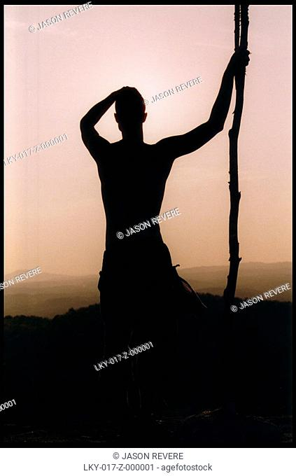 Man holding large stick looks out at sunset