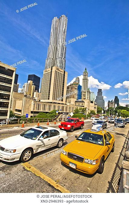 Dented car and taxi, at left Pace University and 8 Spruce Street or Beekman Tower view from Brooklyn Bridge, on background Lower Manhattan skyscraper