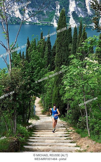 Italy, Trentino, woman running on stairs at Lake Garda