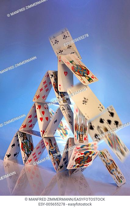 Falling house of cards together as a symbol of collapse