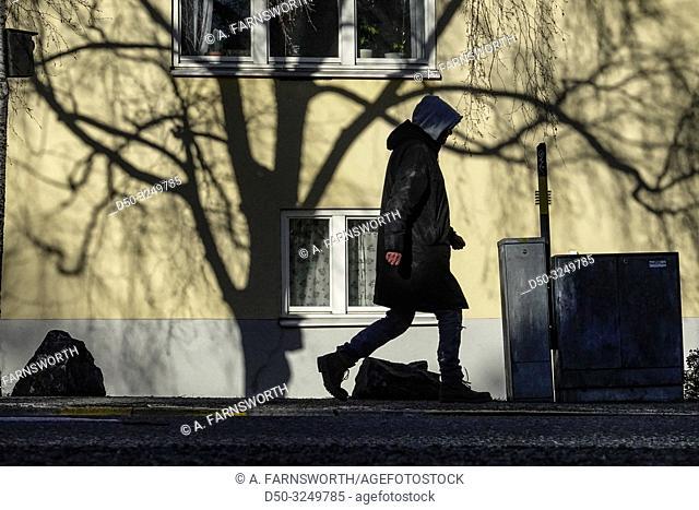 Stockholm, Sweden A man walking in neighborhood of Hägersten on Bäckvägen