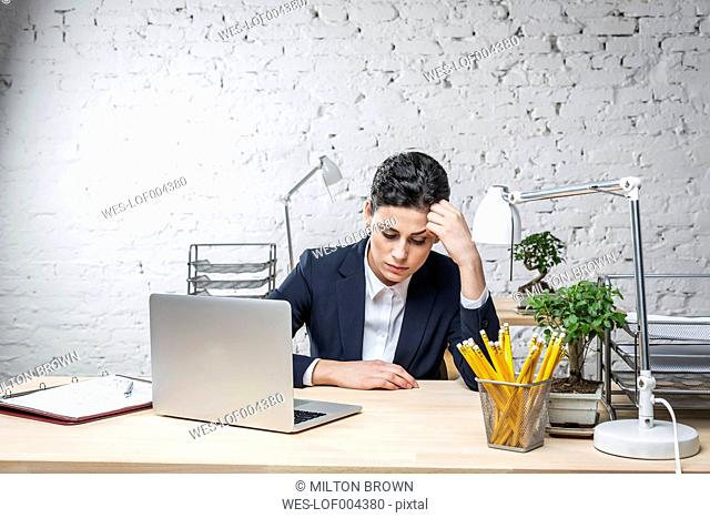 Sad businesswoman at desk with laptop
