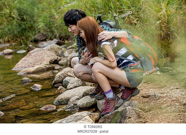 Side view of couple trekkers sitting at stream