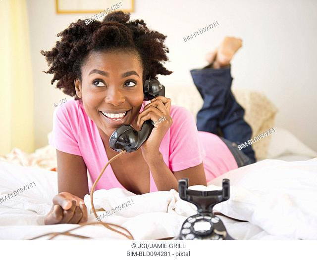 Black woman laying in bed talking on old-fashioned telephone