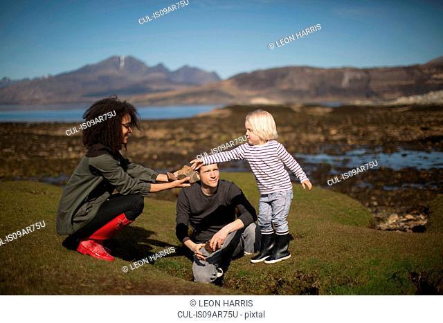 Mother showing son rock, Isle of Skye, Hebrides, Scotland