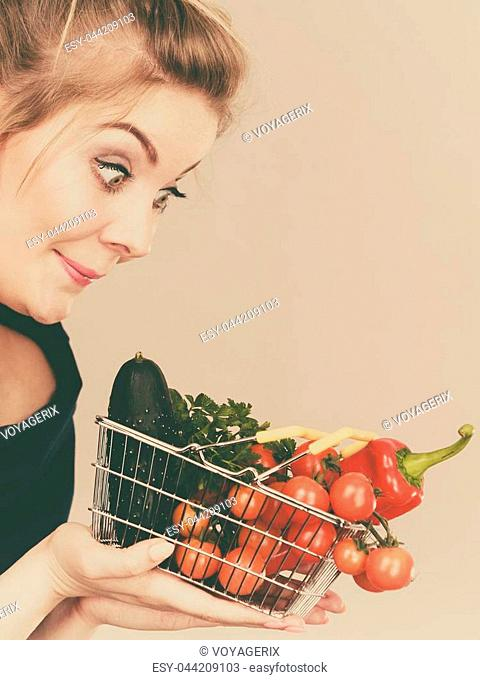 Buying good food, vegetarian products. Positive funny woman holding shopping basket with green red vegetables inside, recommending healthy high fibre diet