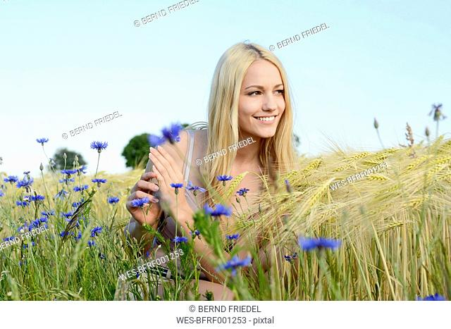 Smiling young woman crouching in a field