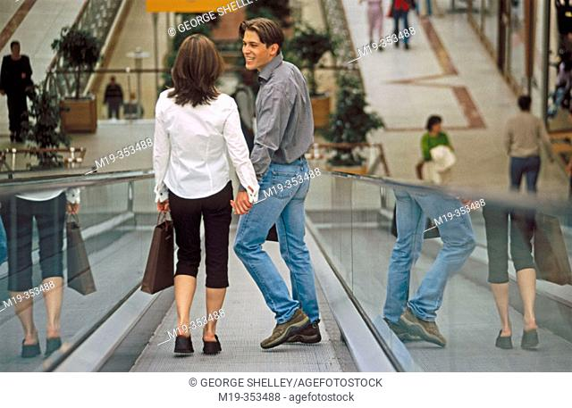Couple with shopping bags on scalator in shopping mall
