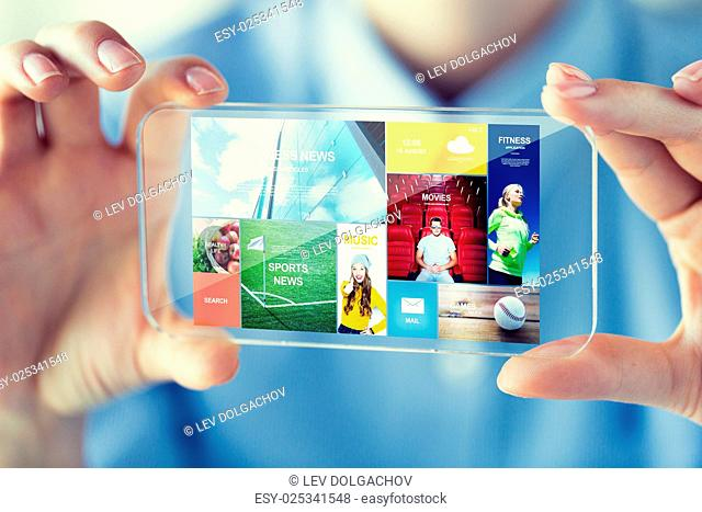 business, technology, media and people concept - close up of woman hand holding and showing transparent with internet applications on screen smartphone at...