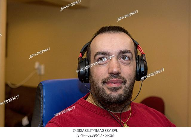 Man with visual impairment listening to his computer