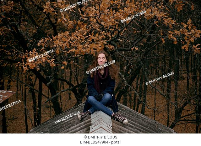Caucasian woman sitting on roof in autumn