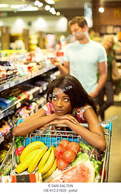 Bored woman pushing full shopping cart in grocery store