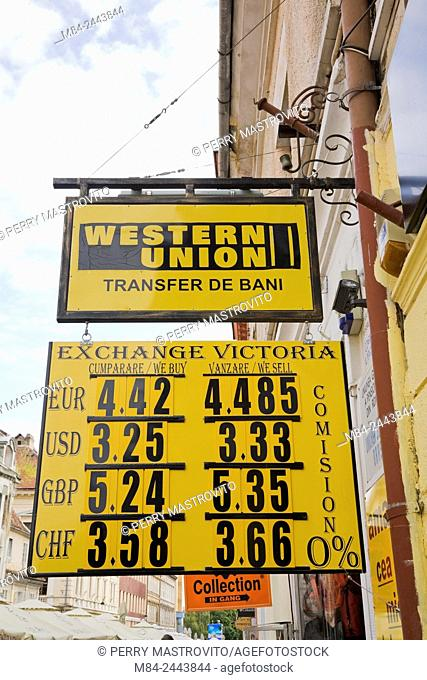 Yellow and black Western Union and Exchange Victoria foreign exchange business signs, Brasov, Romania, Eastern Europe
